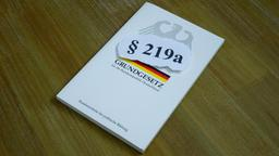 Auf dem Grundgesetz liegt die Schrift § 219a | Bild:dpa / pa / Sascha Steinach