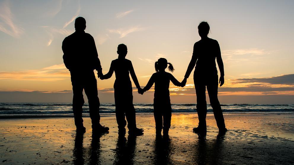 Silhouetten von Eltern mit zwei Kindern am Strand vor Abendhimmel   Bild:pa/dpa/Patrick Pleul
