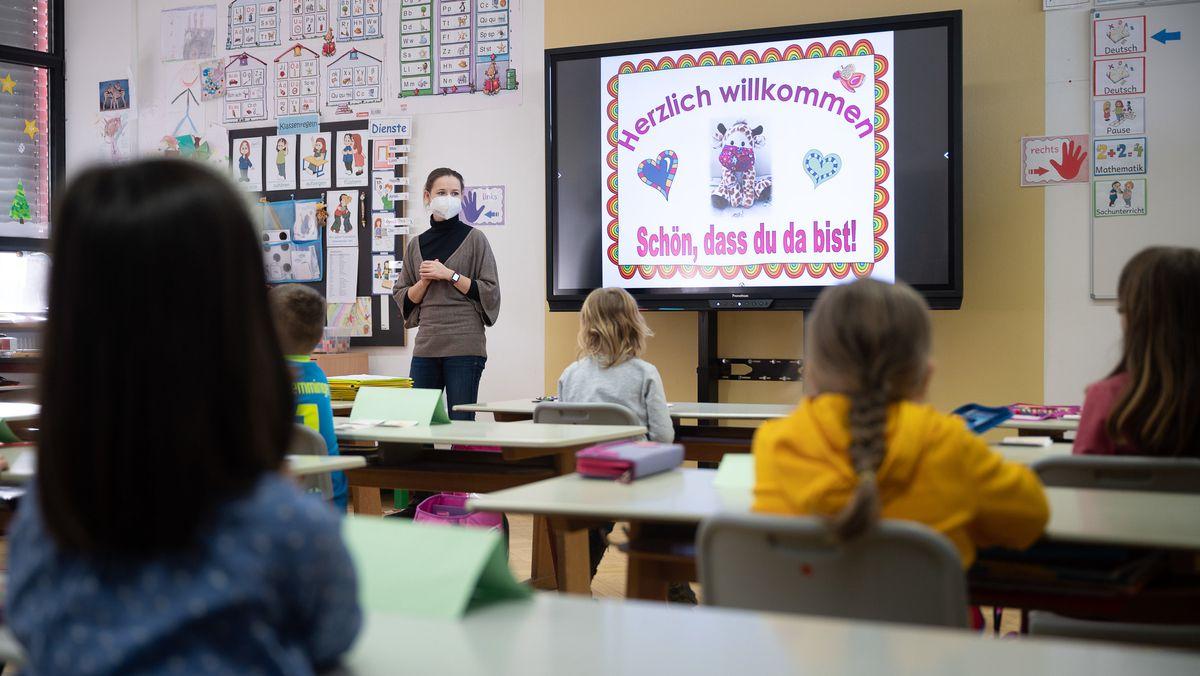 An einer Grundschule mit Wechselunterricht: Eine Lehrerin mit FFP2-Maske steht vor sitzenden Schülern der ersten Klasse in einem Klassenraum und unterrichtet.