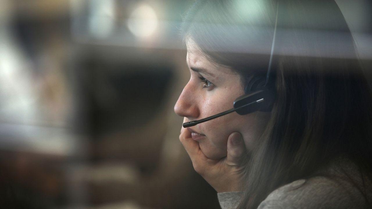 Eine Frau mit Kopfhörer und Mikrofon sitzt in einem Call-Center.