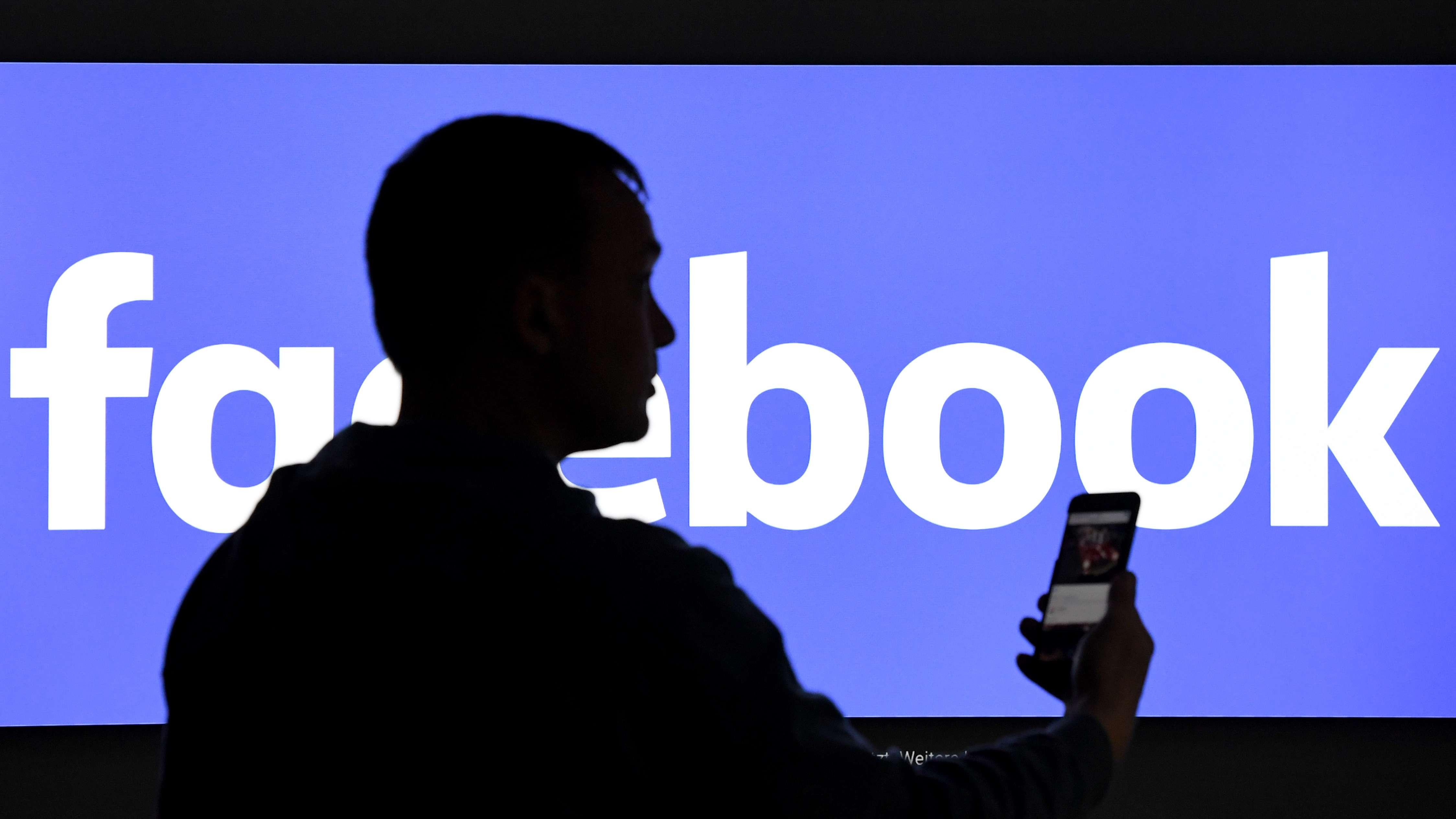 Symbolbild: Ein Mann mit Handy vor einem Facebook-Logo