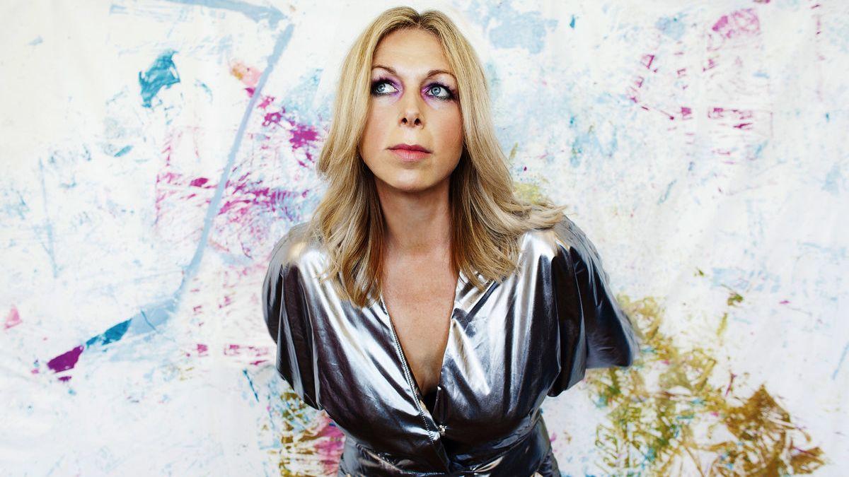 Die Musikerin Jane Weaver im Silberkleid vor einer mit bunter Farbe bespritzten Wand