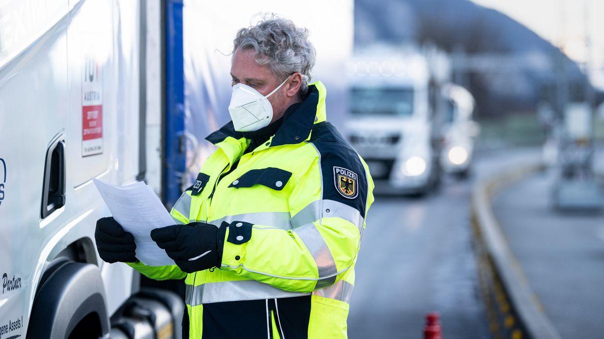 Ein Bundespolizist kontrolliert Dokumente eines LKW-Fahrers an der Autobahn A93 bei Kiefersfelden in Richtung Deutschland.