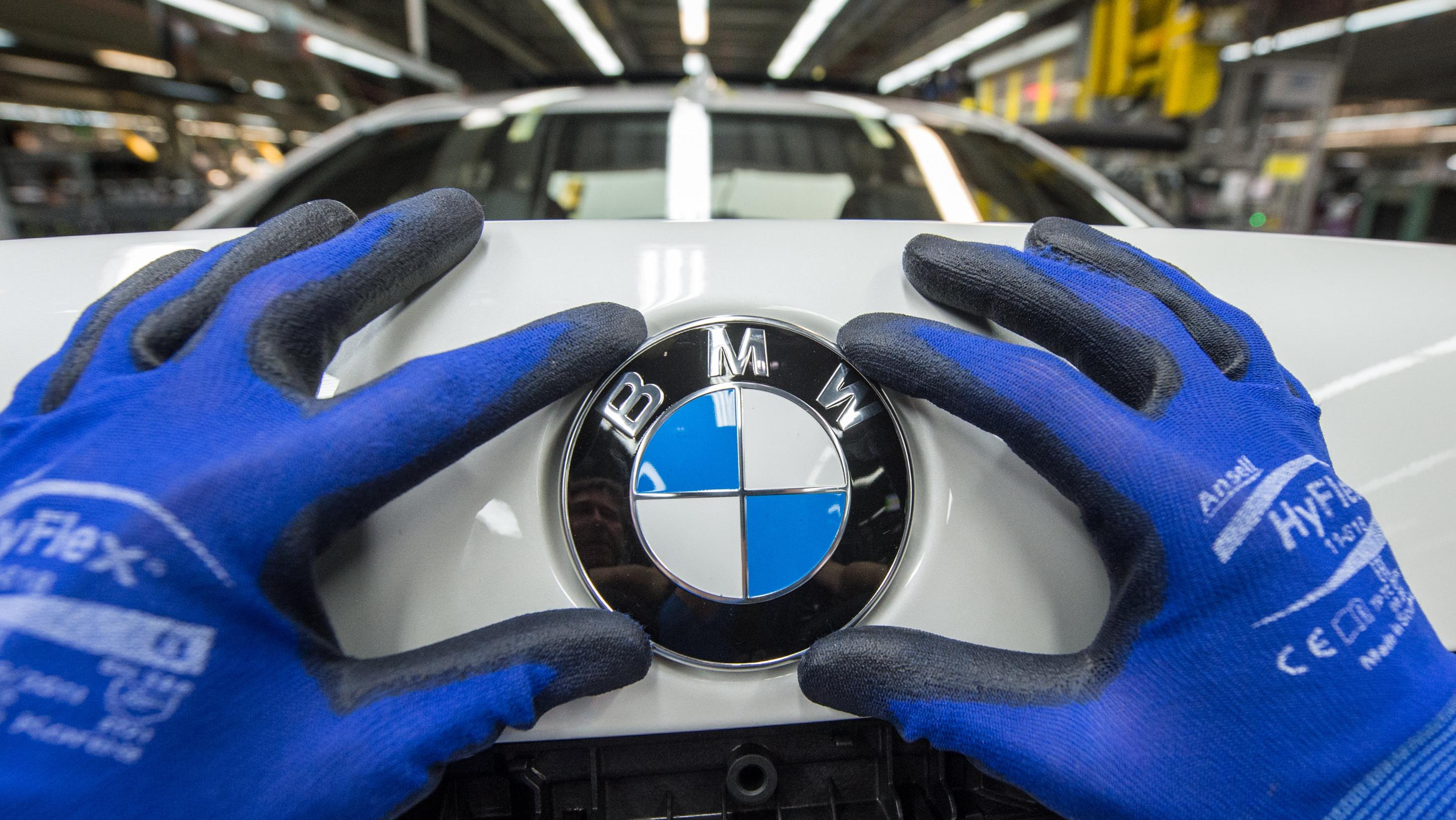 Ein Mitarbeiter montiert ein BMW-Emblem auf den Kofferraumdeckel eines Fahrzeugs der 7er Reihe