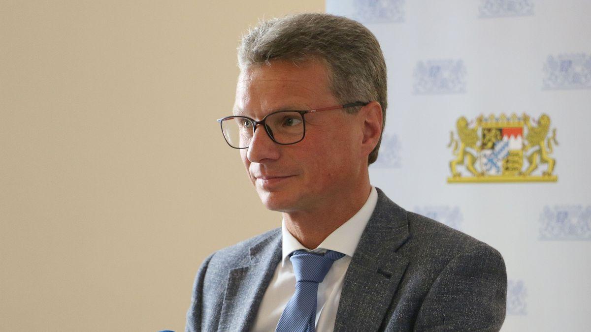 Der bayerische Kunstminister Bernd Sibler blickt, vor dem bayerischen Wappen stehend, aus dem Bild heraus