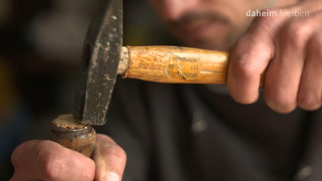 Ein Künstler arbeitet mit dem Hammer an einem Werk