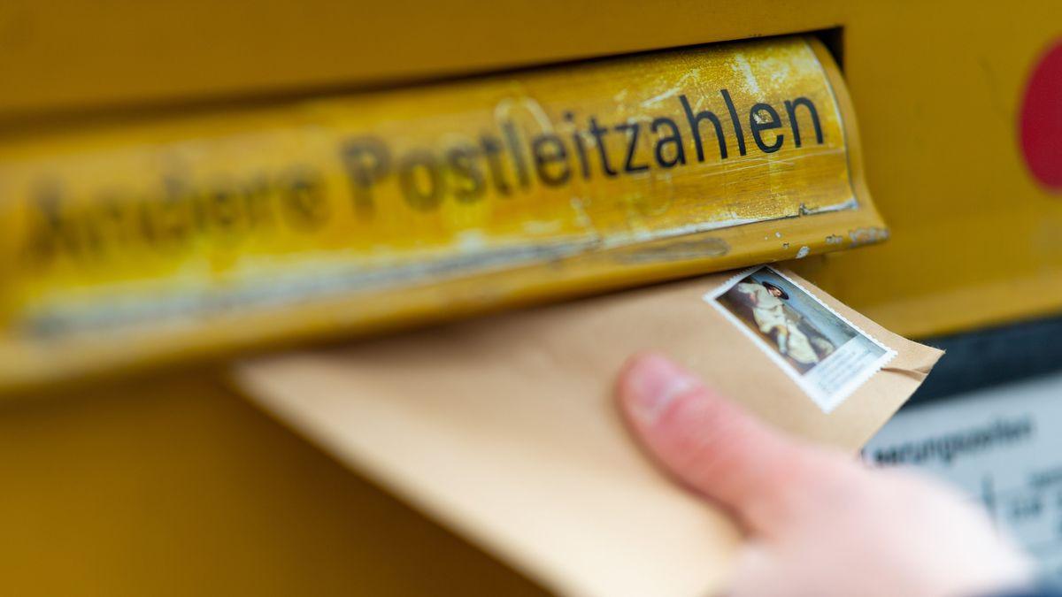 Ein Mann wirft einen Brief in einen Briefkasten