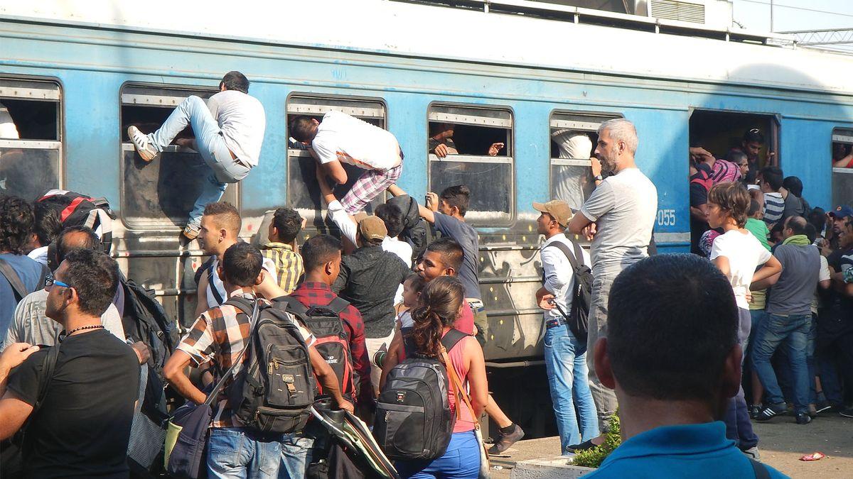 Flüchtlinge versuchen einen überfüllten Zug zu besteigen