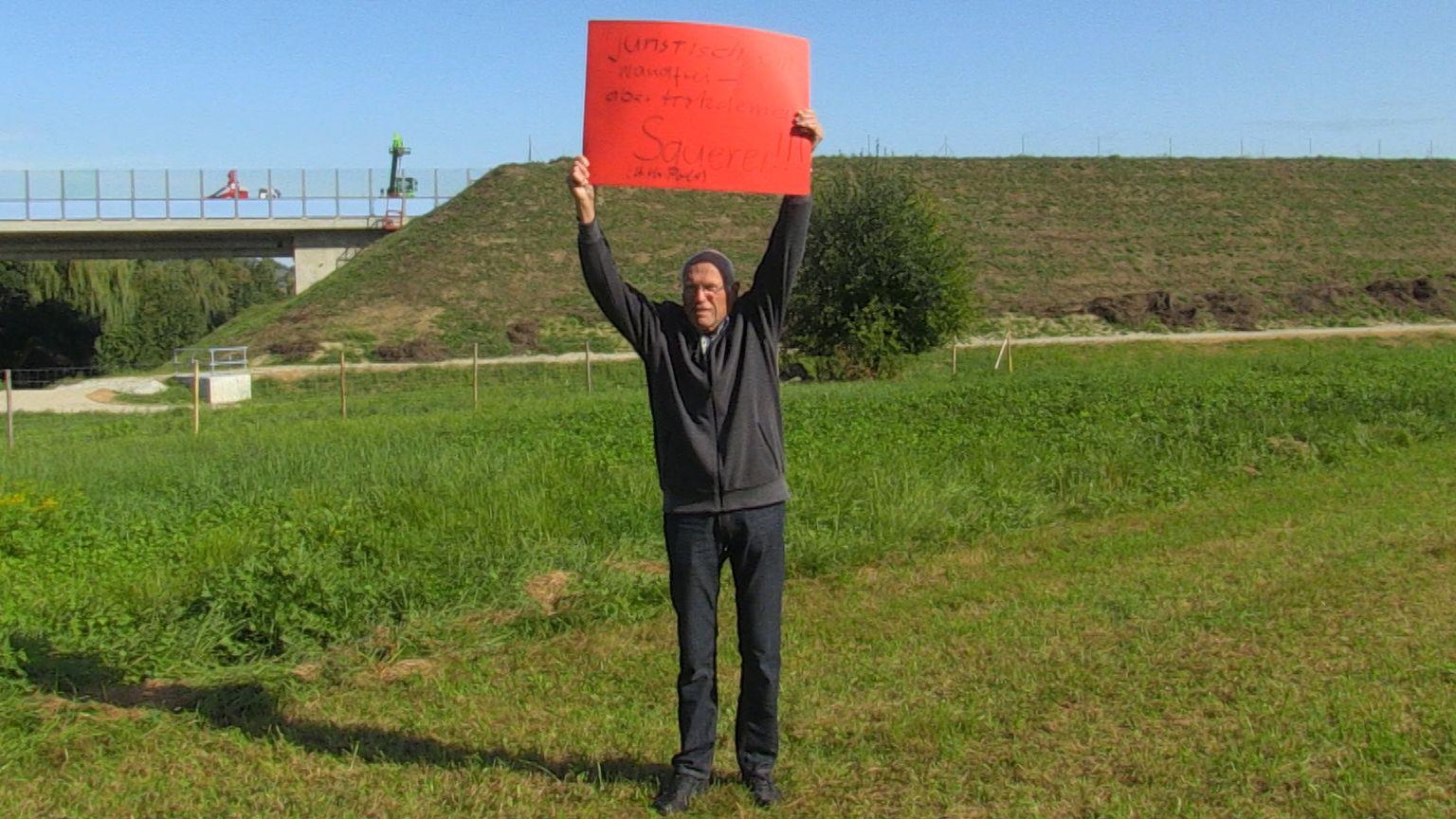 Jörg Asperger mit einem Protestschild gegen die Isentalautobahn