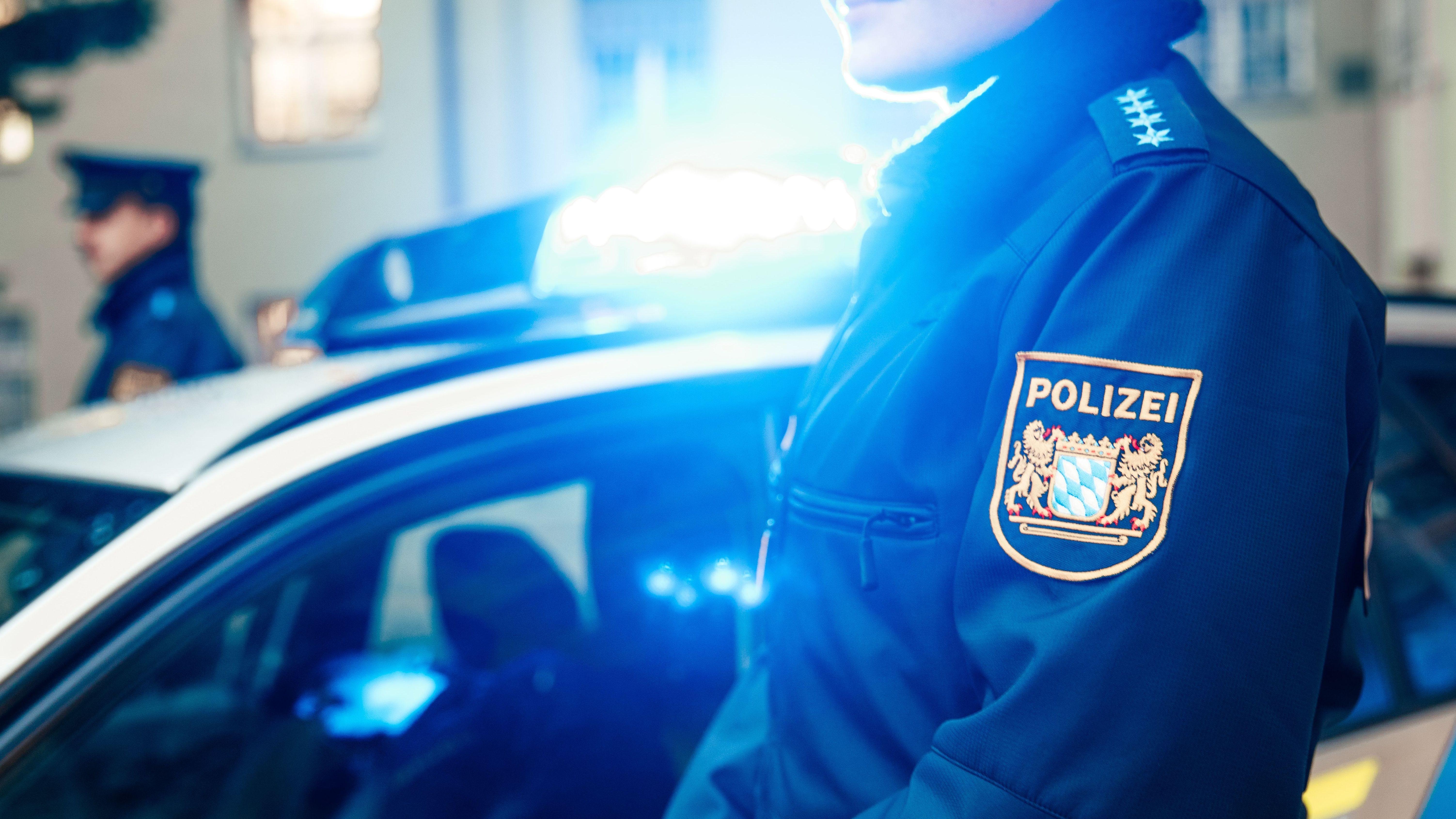 Ein Polizeibeamter steht vor einem Einsatzwagen mit eingeschaltetem Blaulicht.