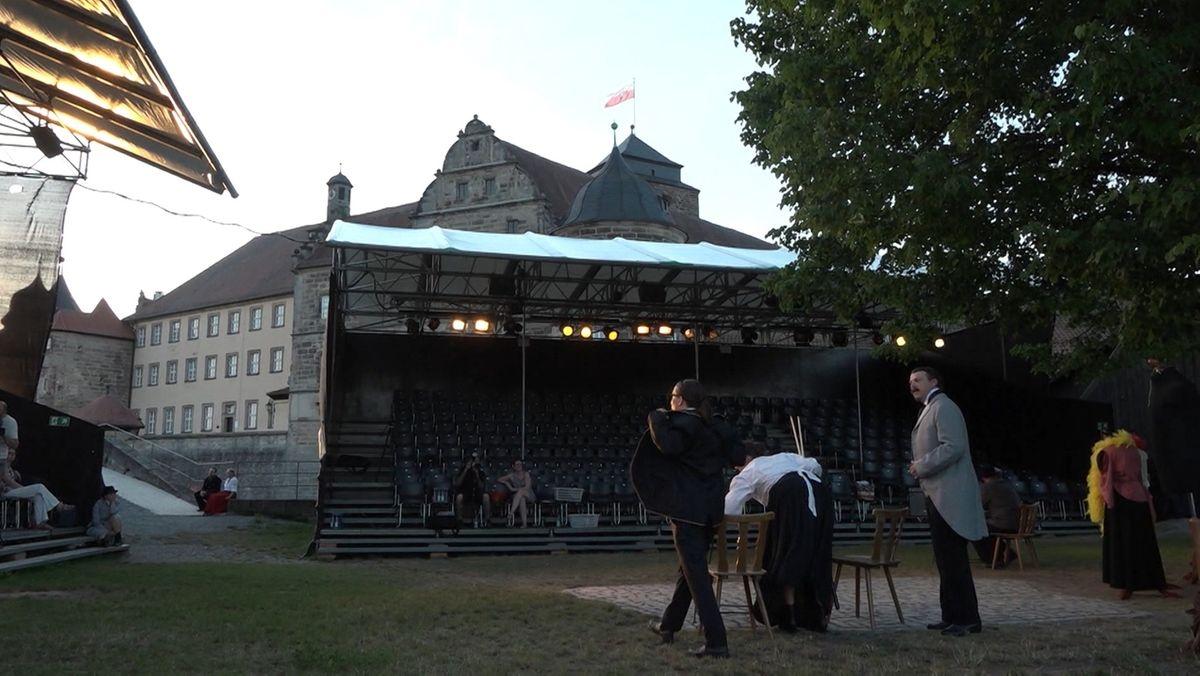 Schauspieler stehen vor der überdachten Bühne, dahinter die Festung Rosenberg.