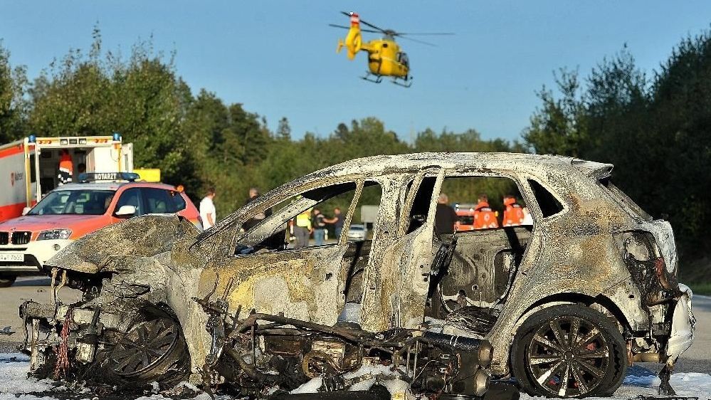 Das ausgebrannte Auto an der Unfallstelle. Beide Fahrzeuge hatten bei dem Zusammenstoß Feuer gefangen.