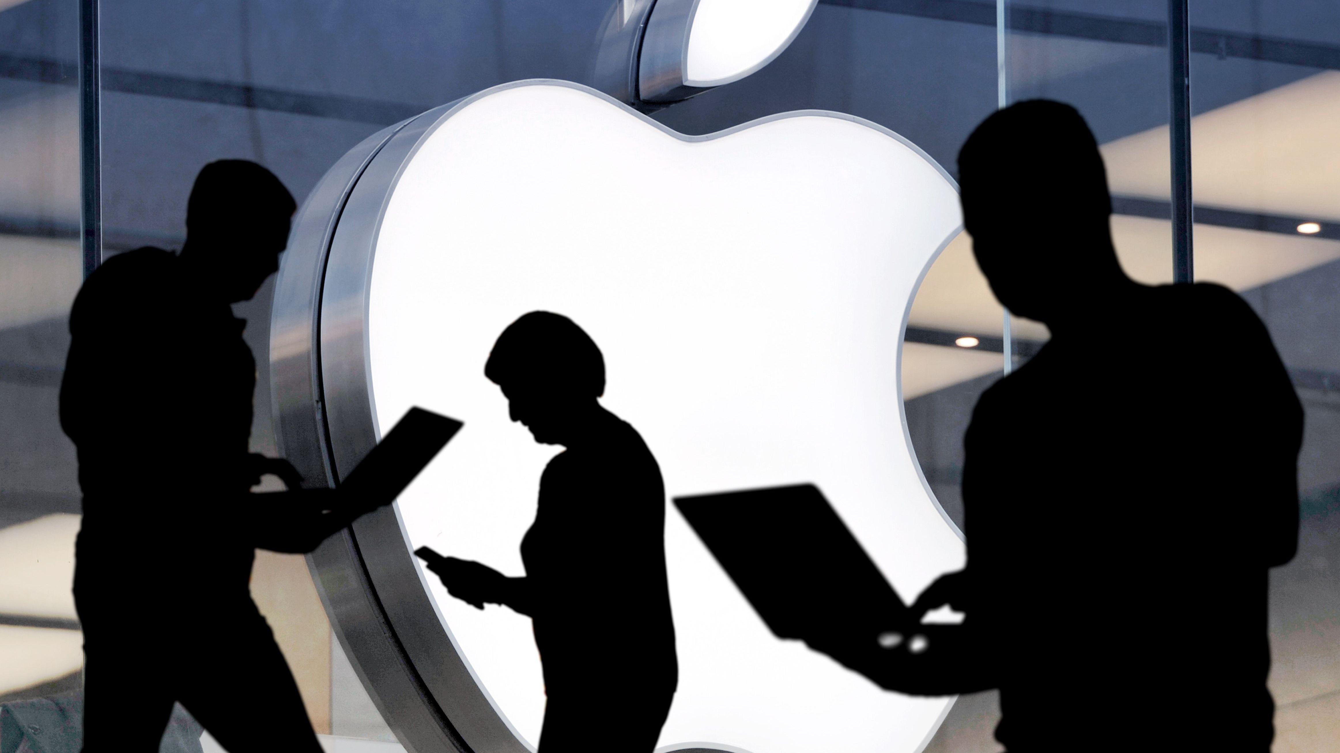 Silhouetten vor einem Apple-Logo (Symbolbild)
