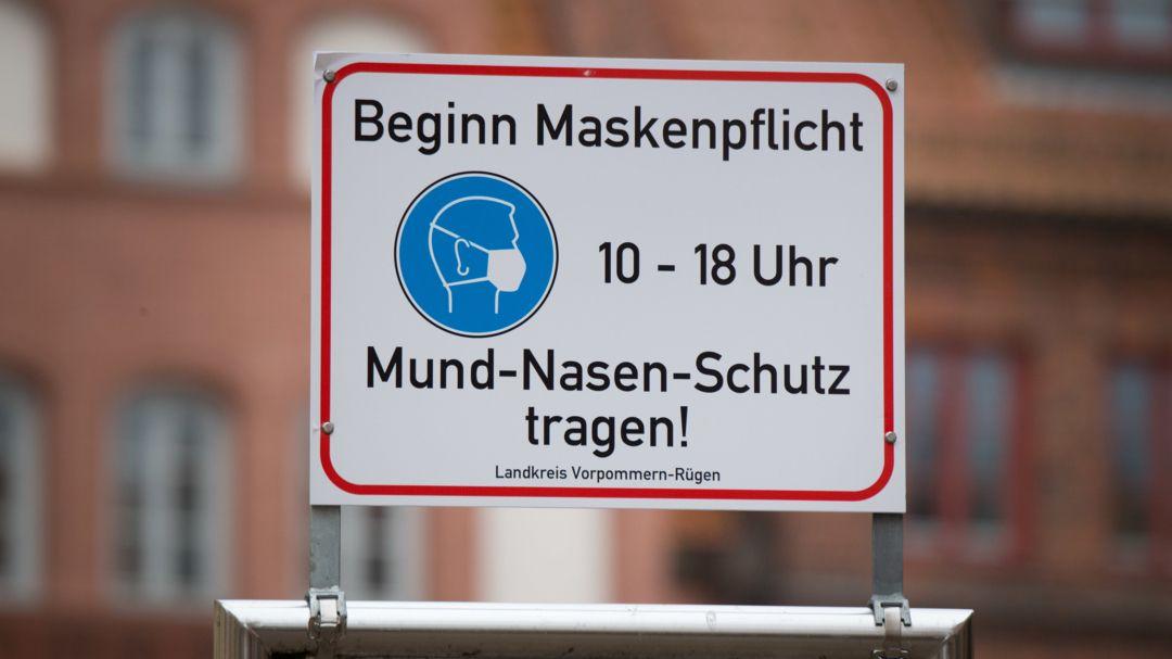 """""""Beginn Maskenpflicht"""" steht auf einem Schild in der Altstadt von Stralsund."""