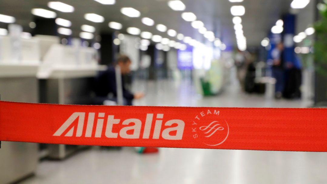 """Ein Absperrband mit der Aufschrift """"Alitalia"""" hängt auf dem Flughafen vor Abfertigungsschaltern."""