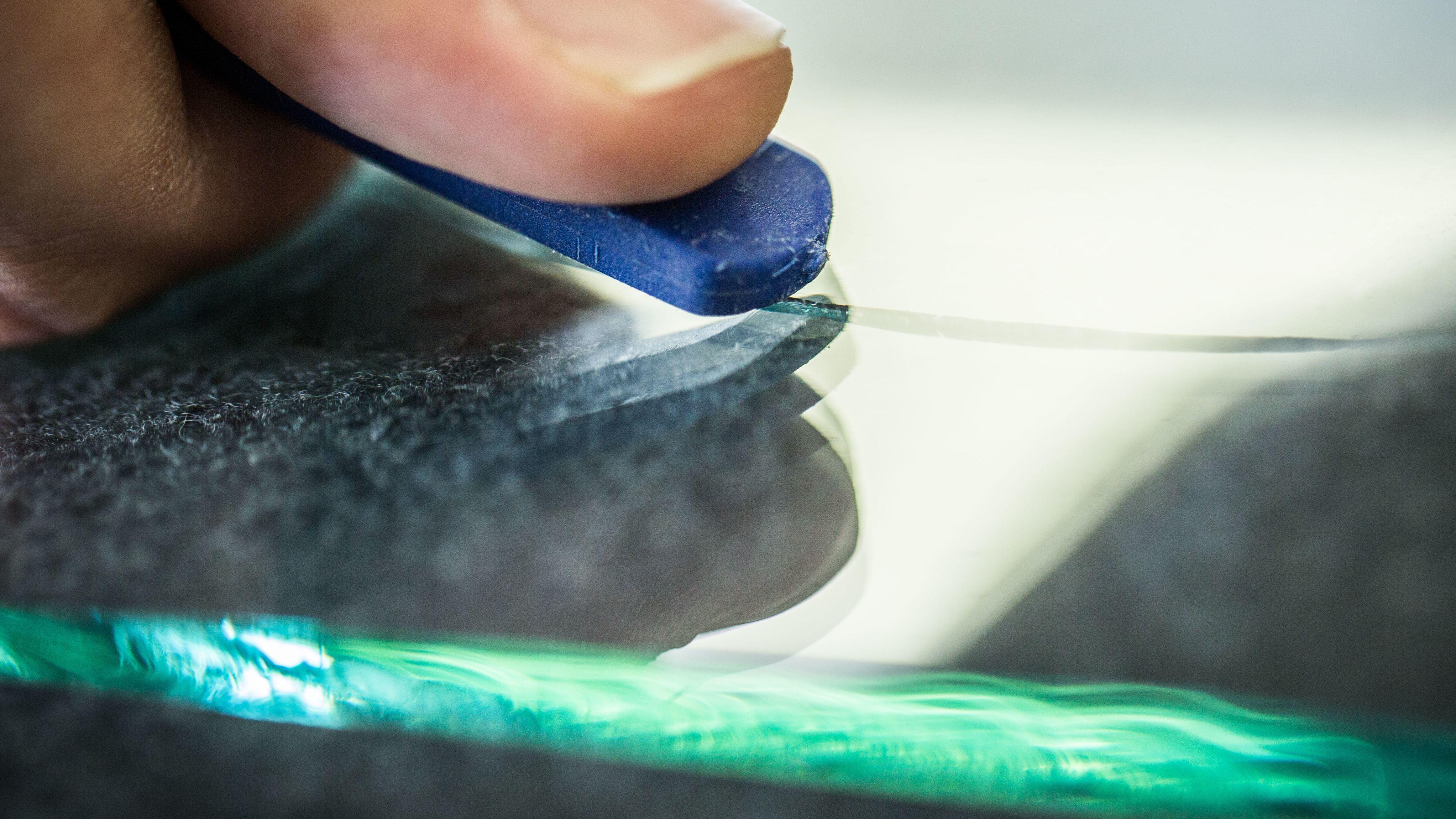 Hand schneidet mit einem speziellen Werkzeug eine Glasscheibe.