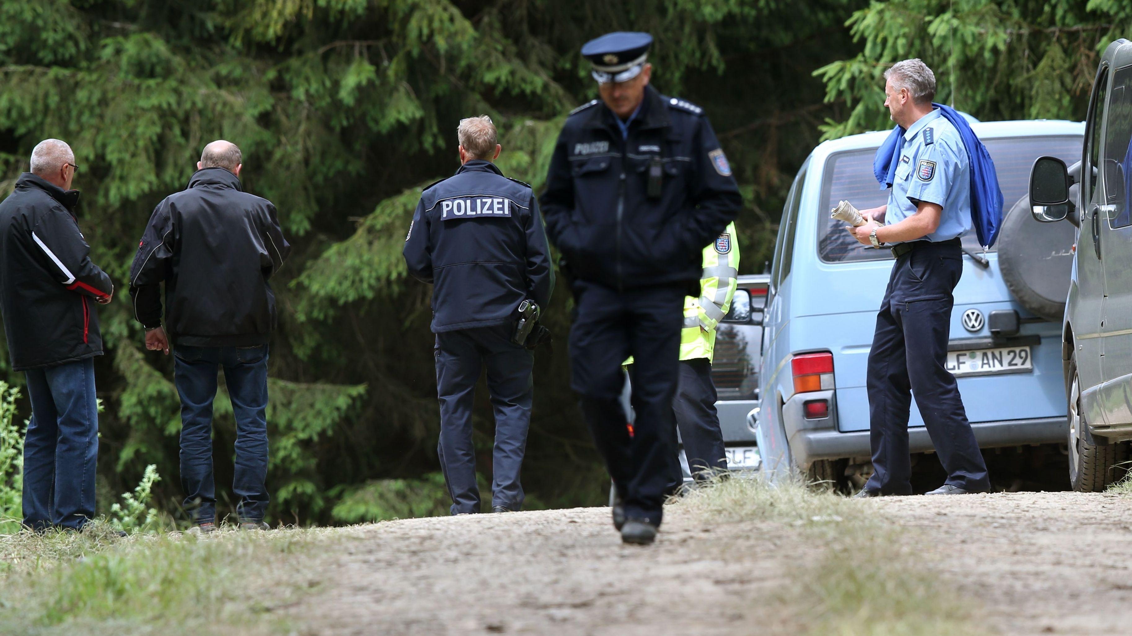 Polizisten stehen auf einem Waldweg.