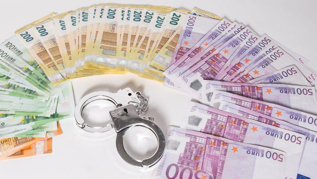 Ausgebreitete Geldscheine und Handschellen