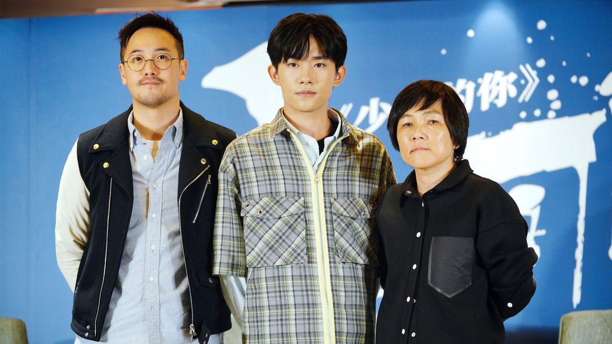 Jackson Yee (Mitte) und Kollegen vor Werbe-Wand