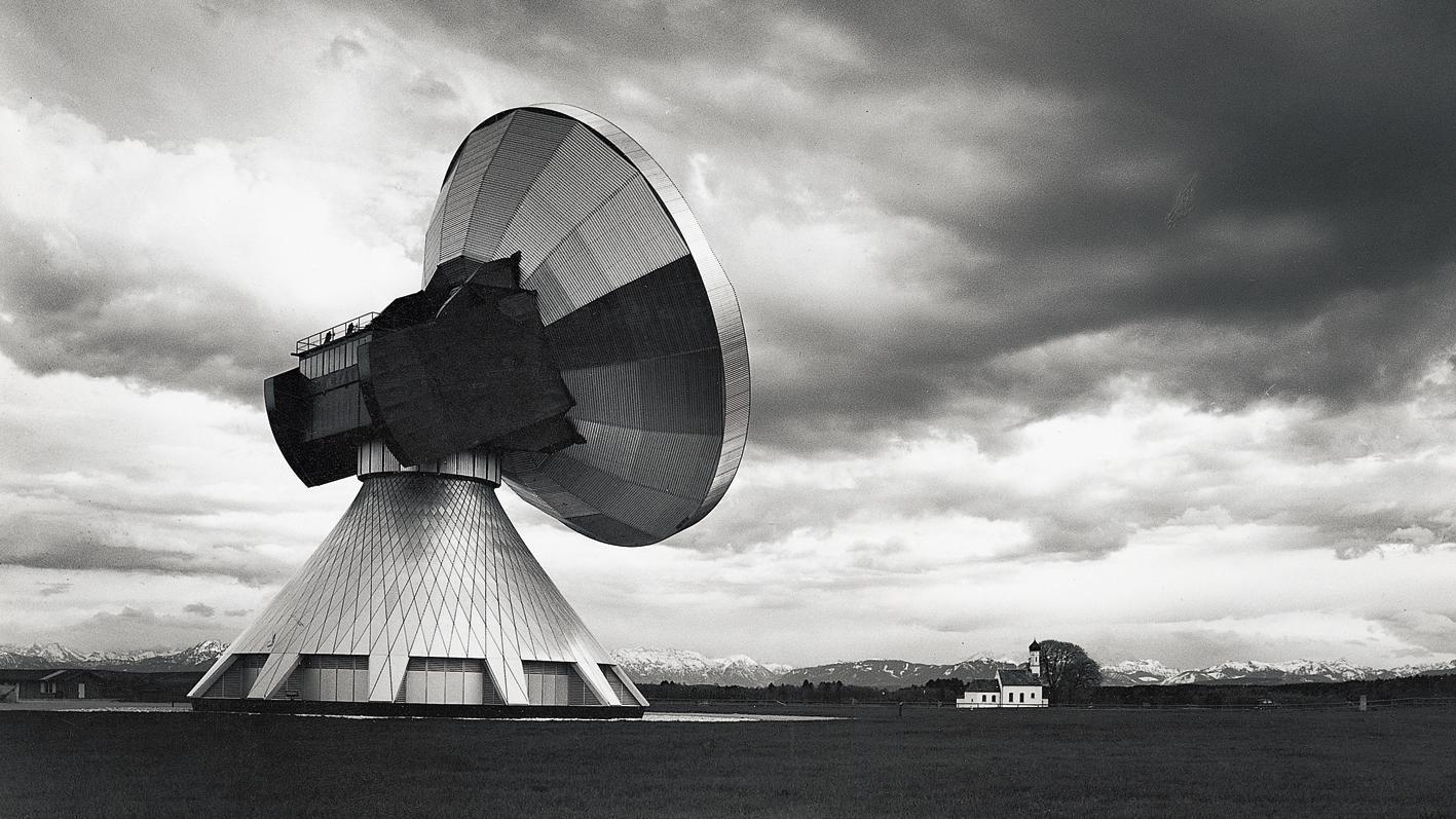 Sigrid Neubert, Erdfunkstelle Raisting: Großer Parabolspiegel einer Antennenanlage neben kleiner Kirche vor bergpanorama