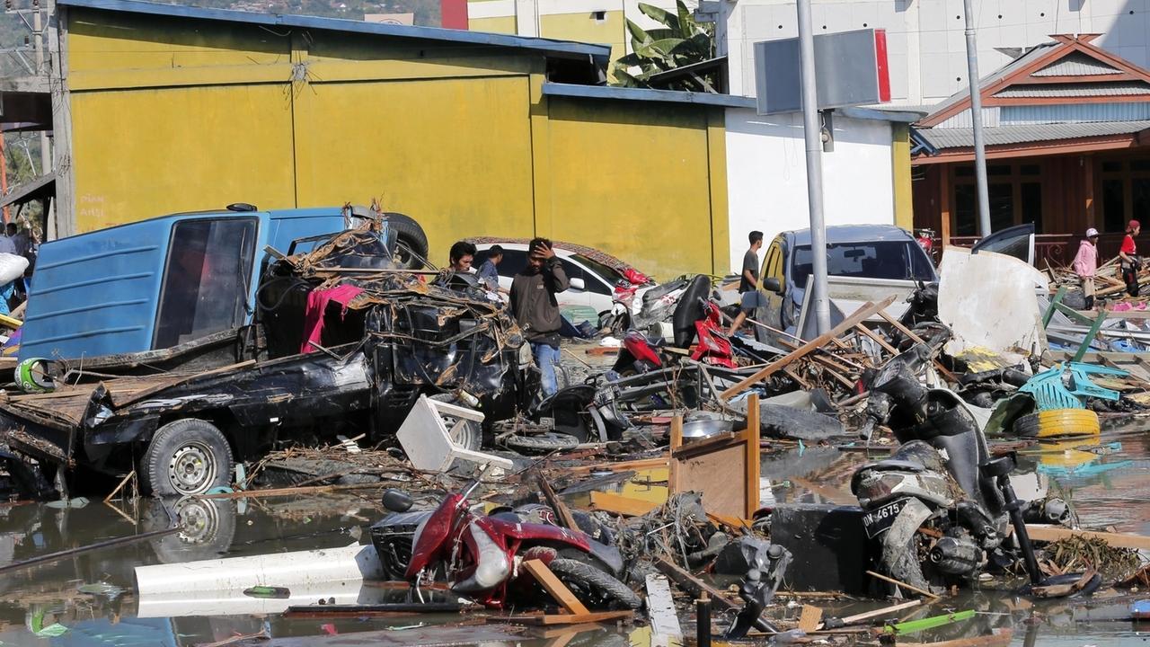 Menschen zwischen Trümmern und zerstörten Fahrzeugen