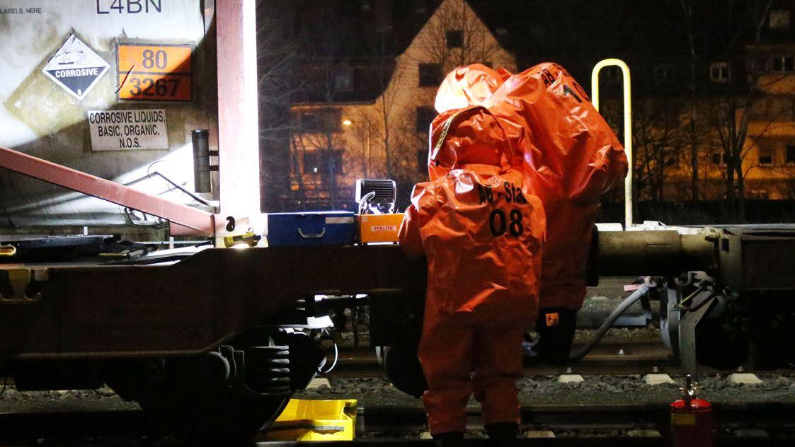 Feuerwehrleute kontrollieren ein feuchtes Ventil an einem Güterwagen in Aschaffenburg