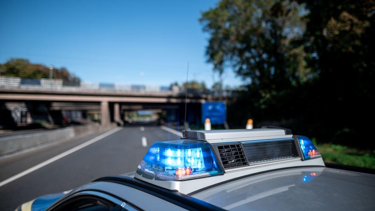 Auf einer gesperrten Autobahn steht im Vordergrund ein Polizeiauto mit eingeschaltetem Blaulicht (Symbolbild).