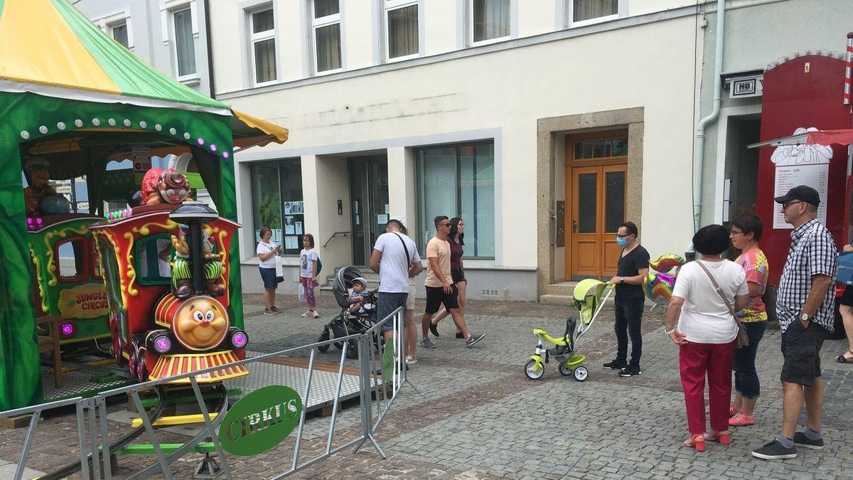 An einem grünen Karussell spazieren Besucher unter anderem mit Kinderwägen vorbei.