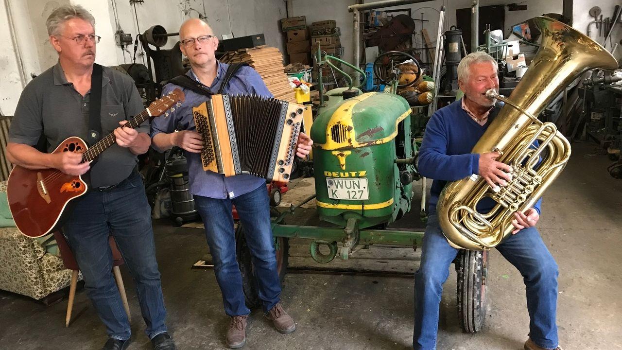 Drei Musikanten mit Instrumenten und einem grünen Traktor.
