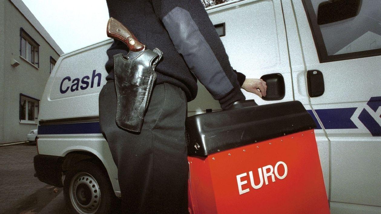 Ein bewaffneter Sicherheitsmitarbeiter bringt eine rote Geldkassette in einen Werttransporter