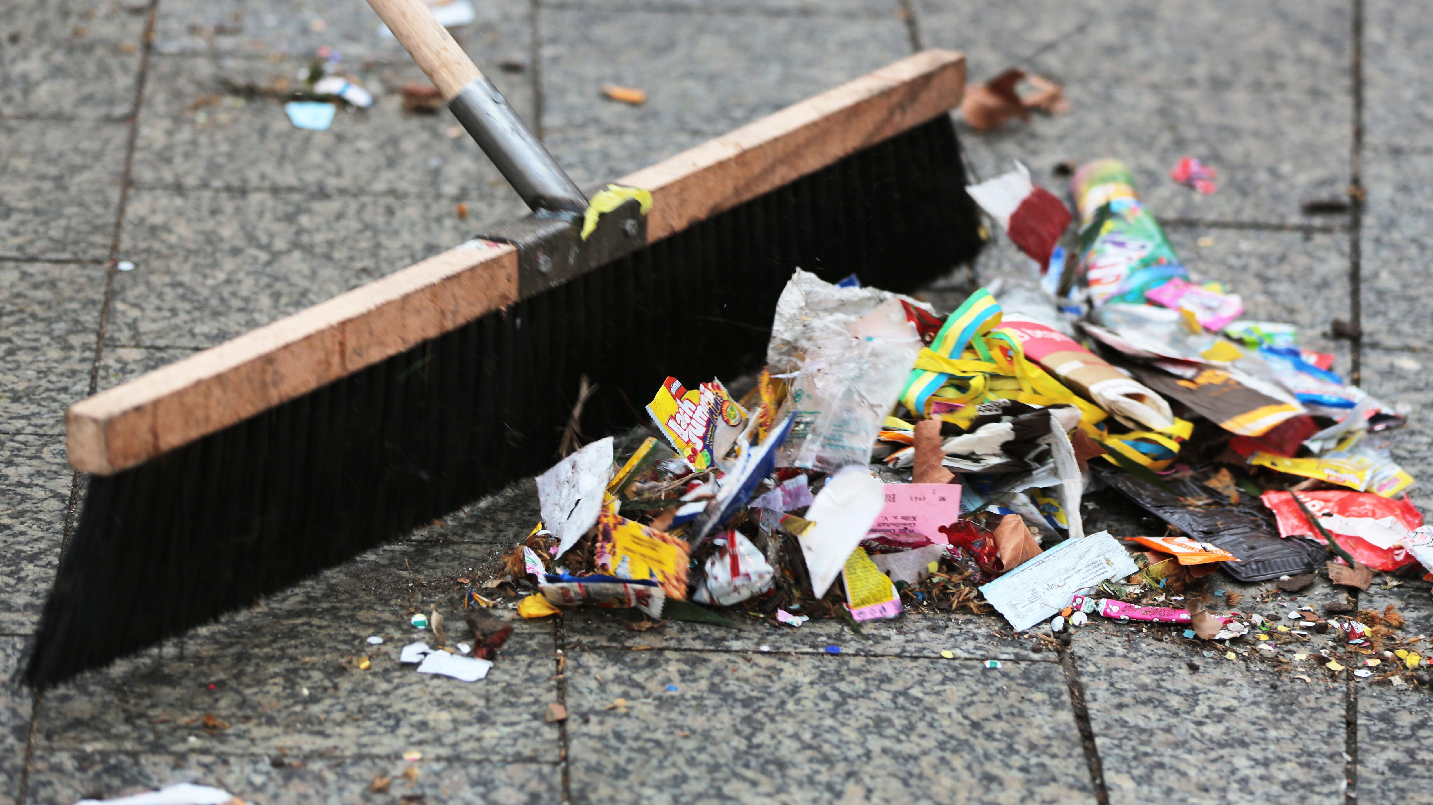 Straßenreinigung: Besen kehrt die Müllreste des Straßenfaschings zusammen
