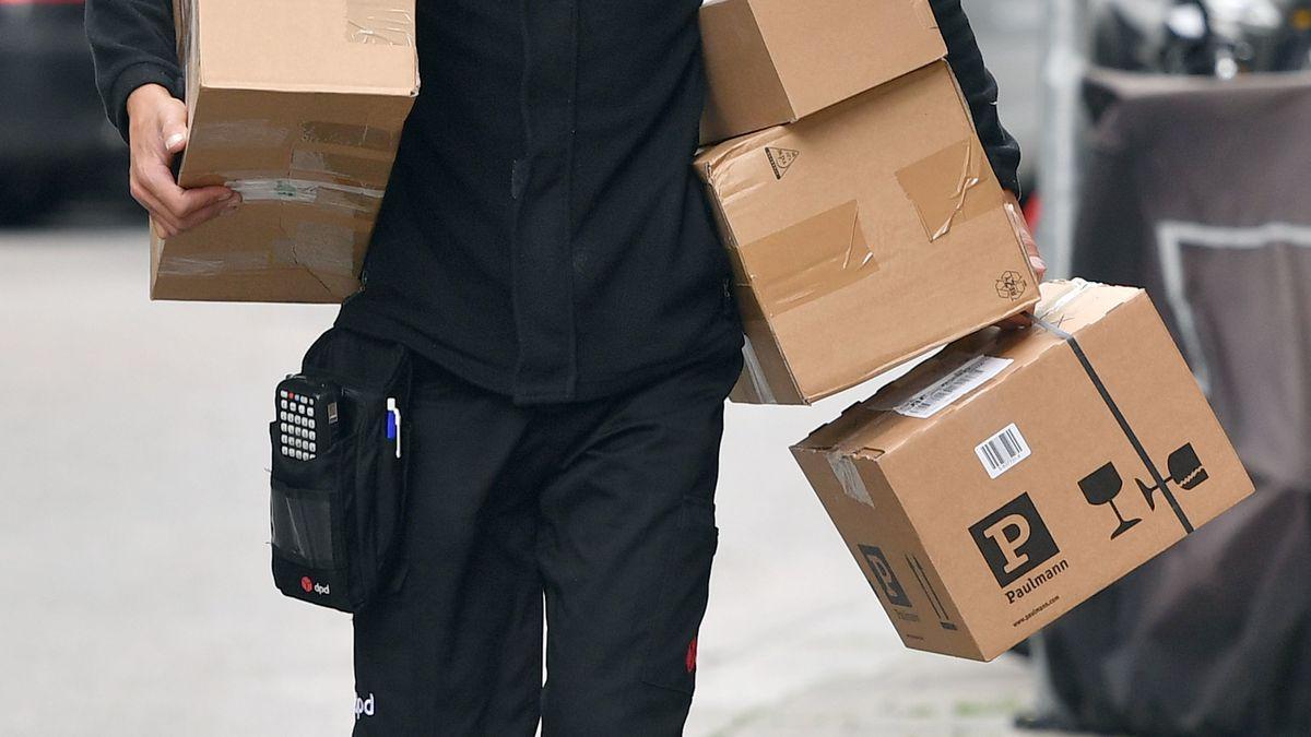 Ein Paketzusteller trägt mehrere Päckchen