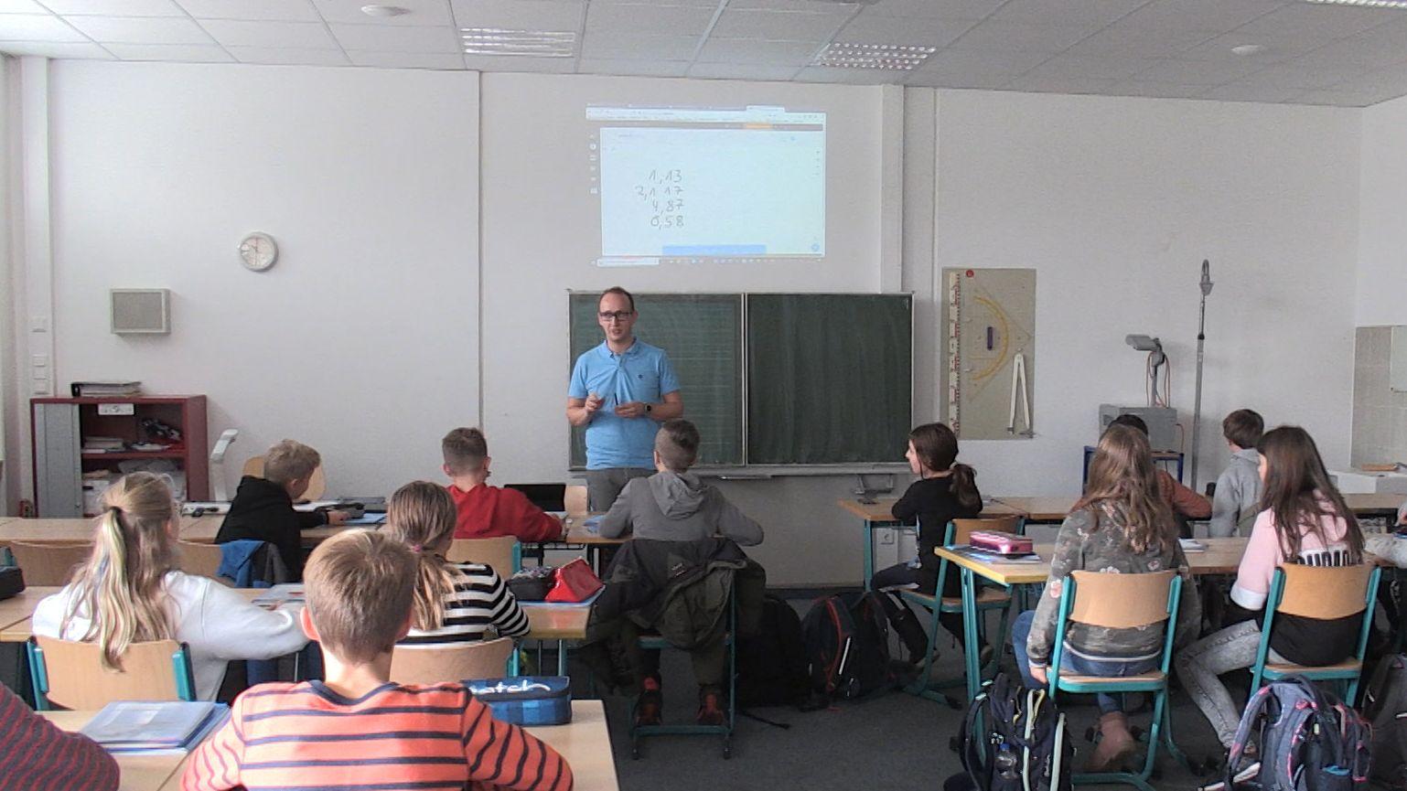 Lehrer im Klassenzimmer mit Schülern.