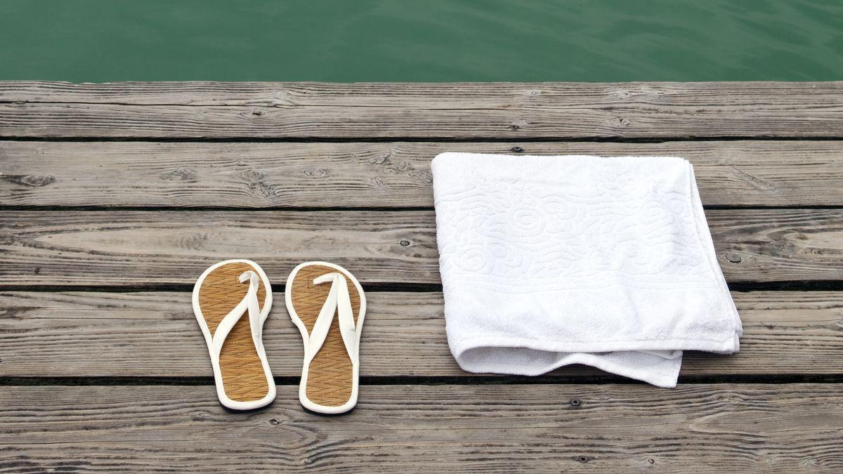 Flip-Flops und Handtuch auf Steg an einem See (Symbolfoto)