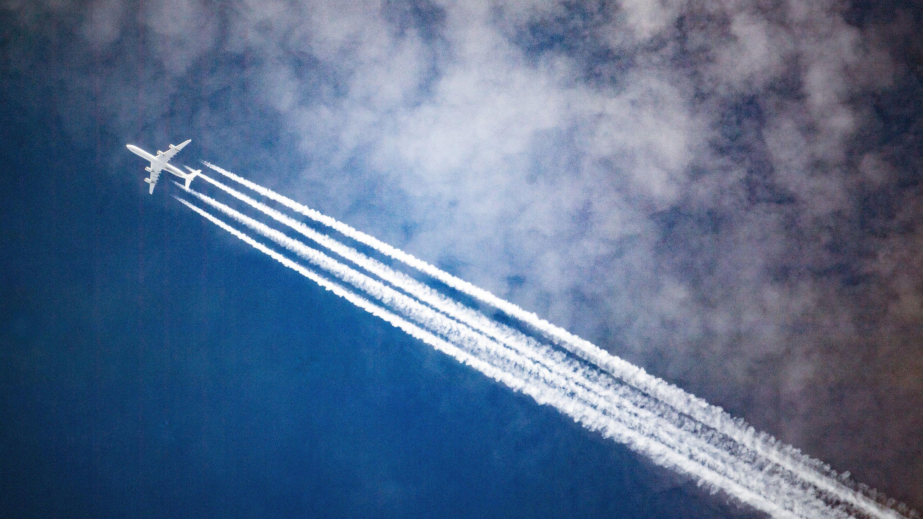 Ein Flugzeug zieht Kondensstreifen hinter sich, während es durch die Wolken fliegt