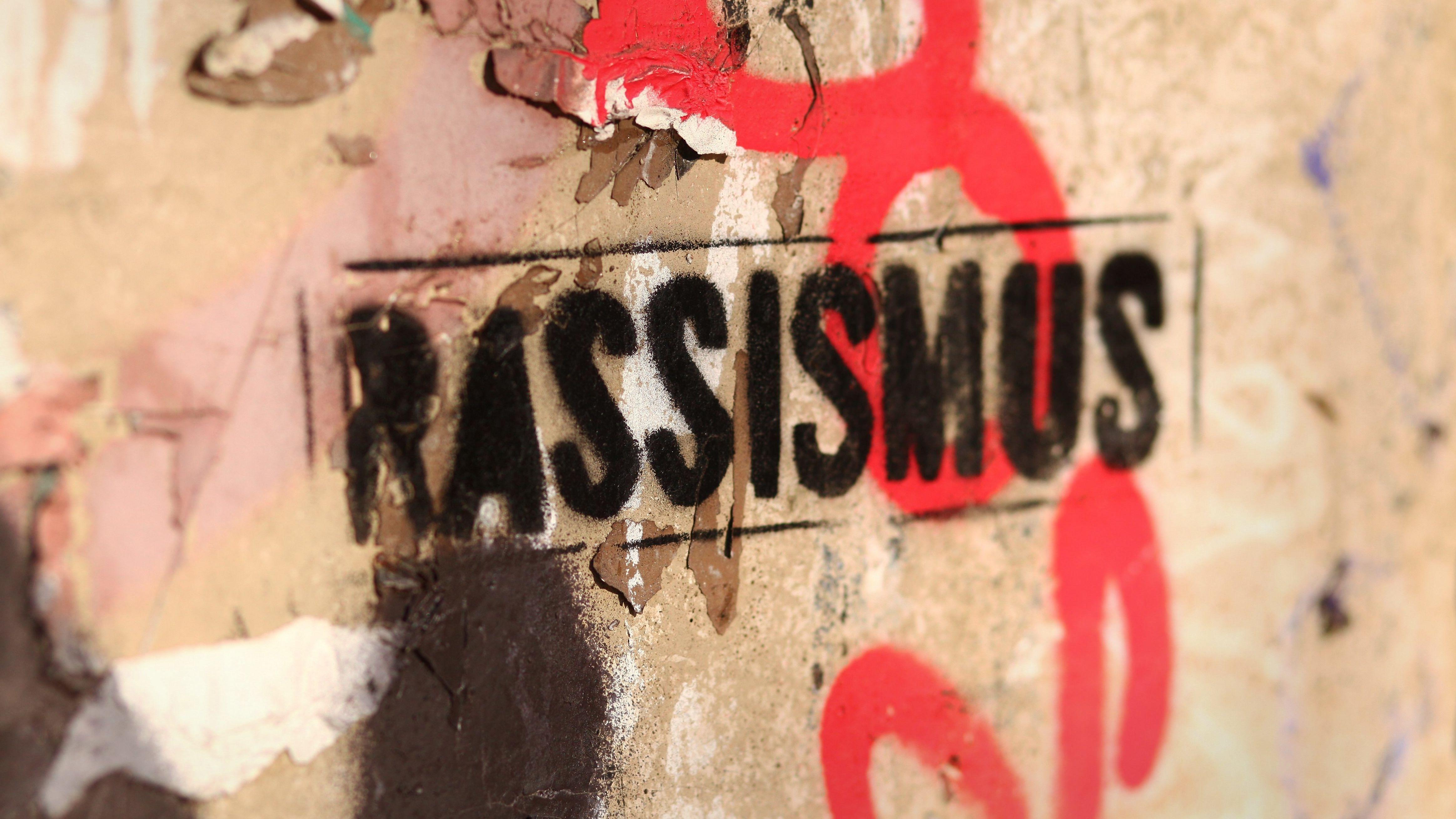 """Das Wort """"Rassismus"""" steht auf einer Mauer"""