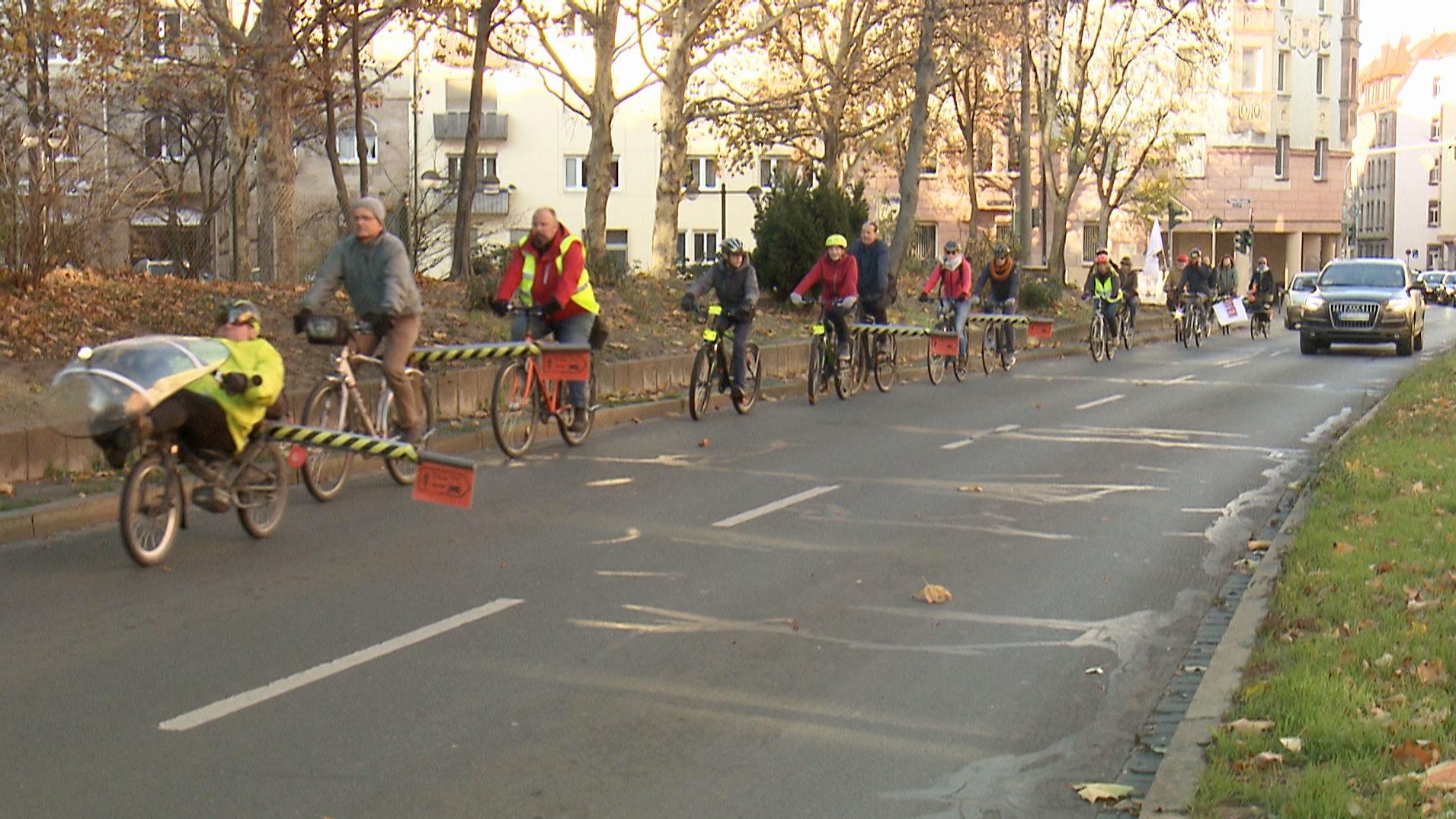 Radfahrer fahren auf einer mehrstreifigen Straße. Einige von ihnen haben inige von ihnen haben Abstandhalter aus Schaumstoff an ihre Gepäckträger montiert. Auf dem linken Fahrstreifen überholt sie ein Auto.