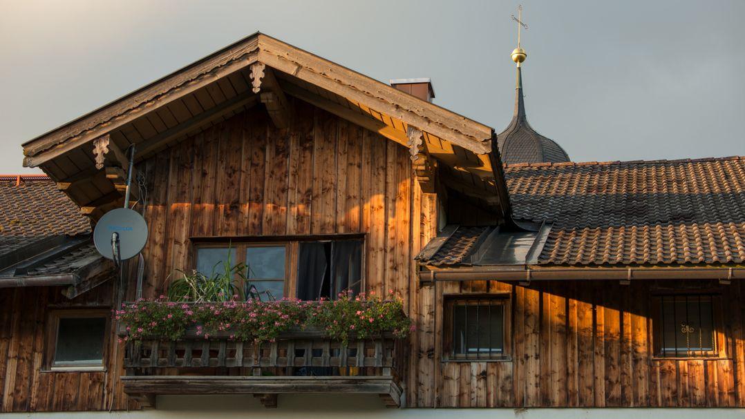 Holzhaus mit Balkon und kleiner Satellitenschüssel.