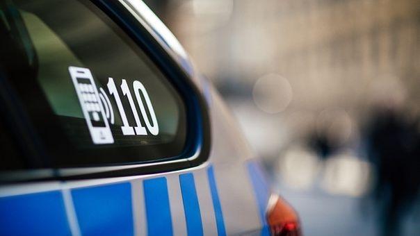Auf einem Polizeiauto klebt ein Aufkleber mit der Notrufnummer 110.