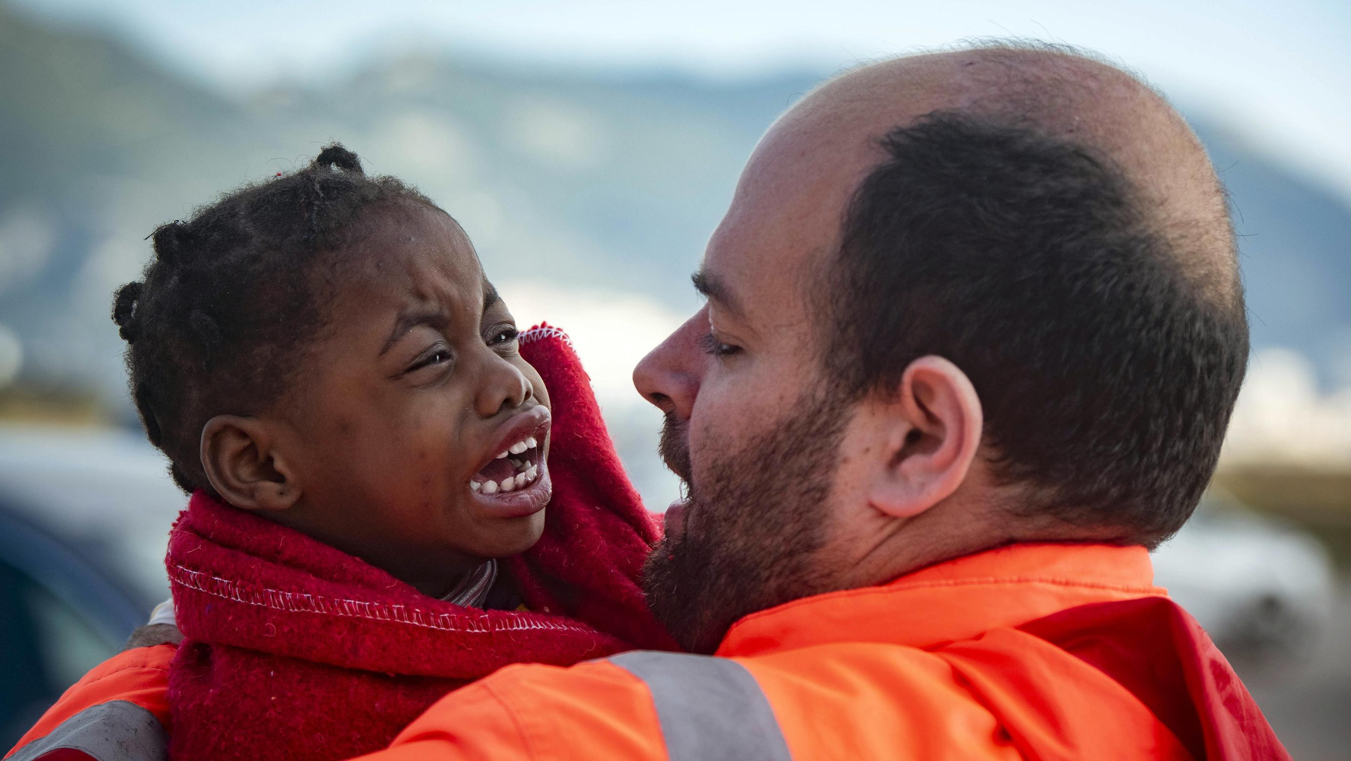 Oktober 2018: Ein Mitarbeiter des spanischen Seenotrettungsdienstes hält ein weinendes Kind im Arm.