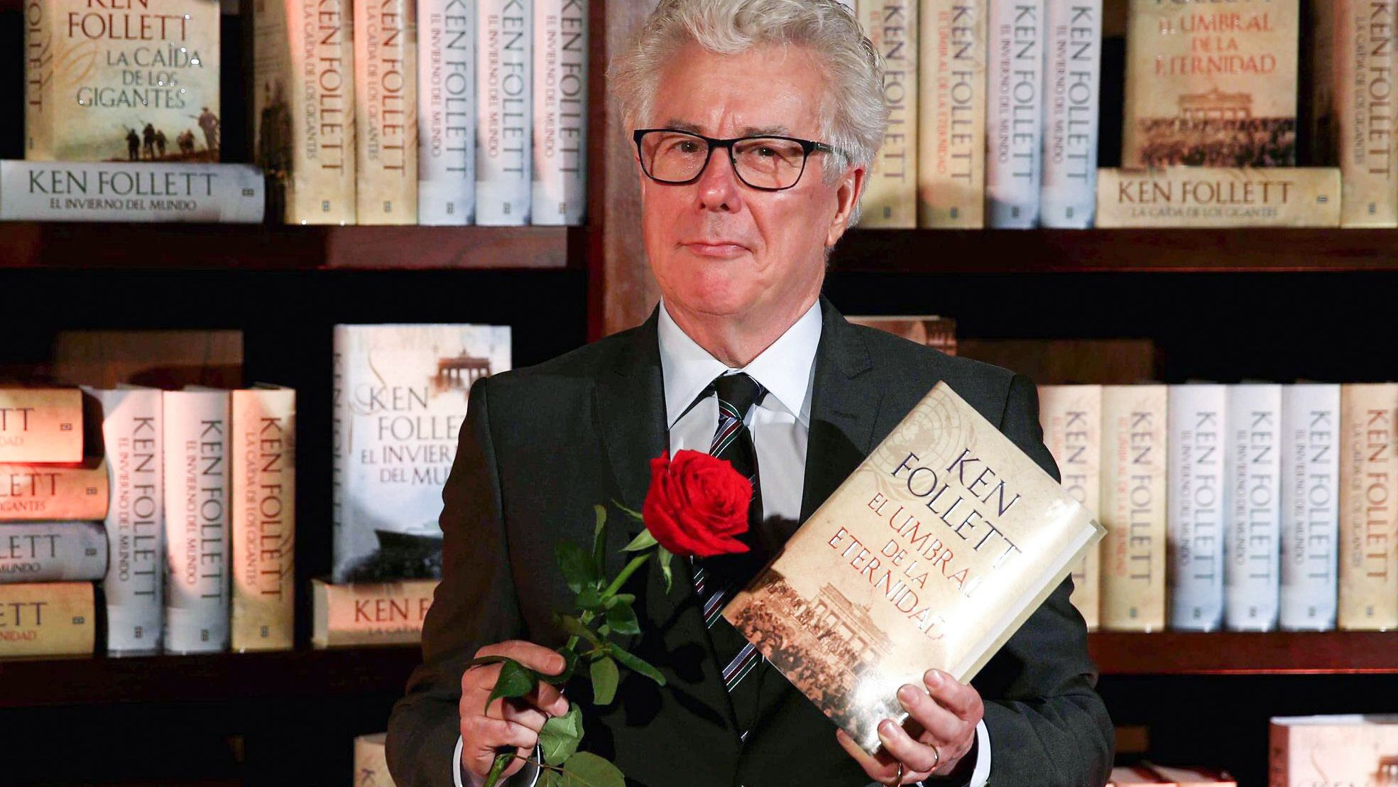 Ken Follett steht vor einem Bücherregal und hält eines seiner Bücher und eine Rose in der Hand.