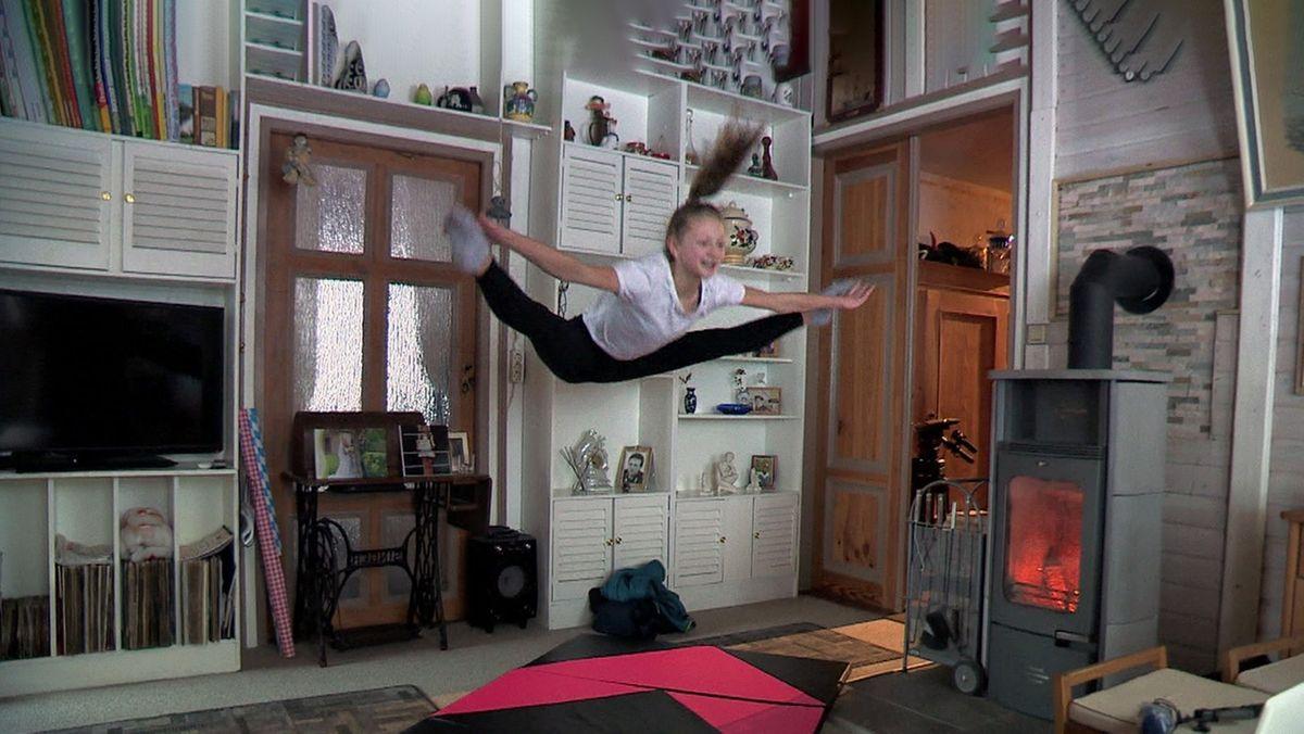 Eine Mädchen springt im Spagat in ihrem Wohnzimmer in die Luft.