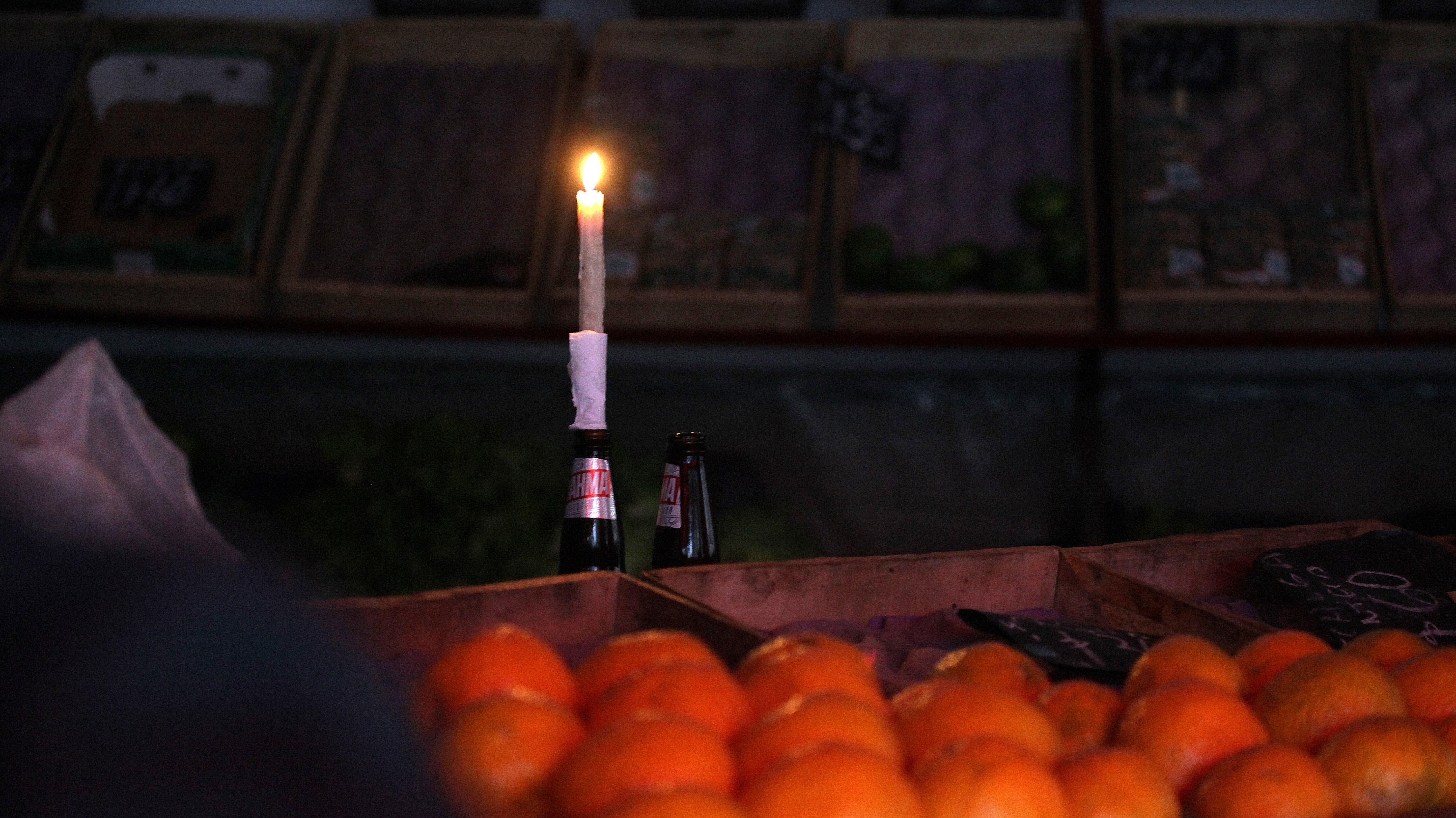Stromausfall in Südamerika: Ein Obsthändler muss seine Waren mit einer Kerze beleuchten.