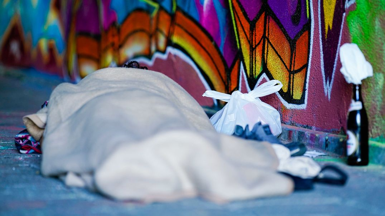 In eine Decke gewickelt schläft ein Obdachloser in einem Brückendurchgang an einer mit Graffiti bemalten Wand.