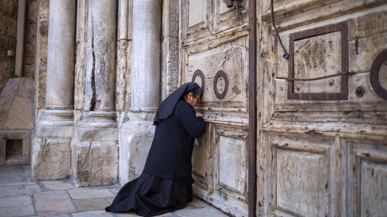 Eine Nonne betet am Gründonnerstag vor der verschlossenen Tür der Grabeskirche.