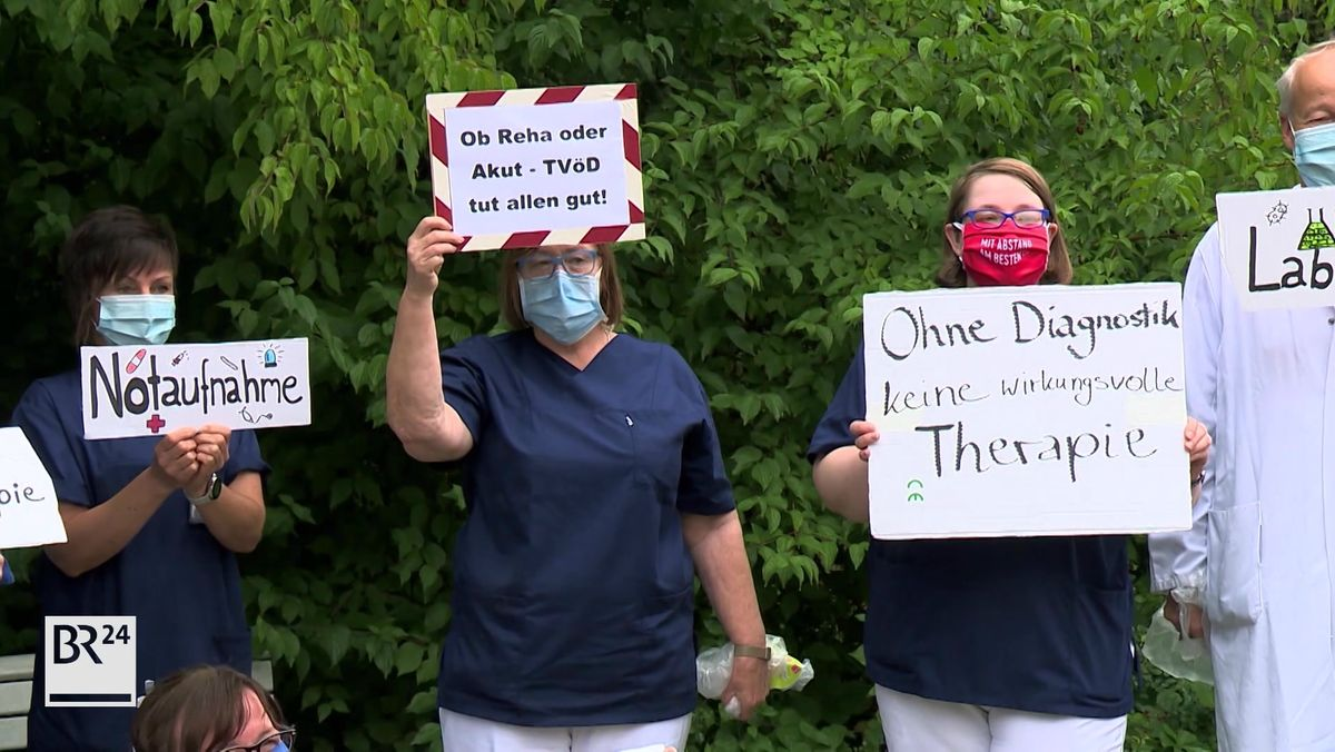 Beschäftigte der Sana Klinik halten Spruchbänder hoch