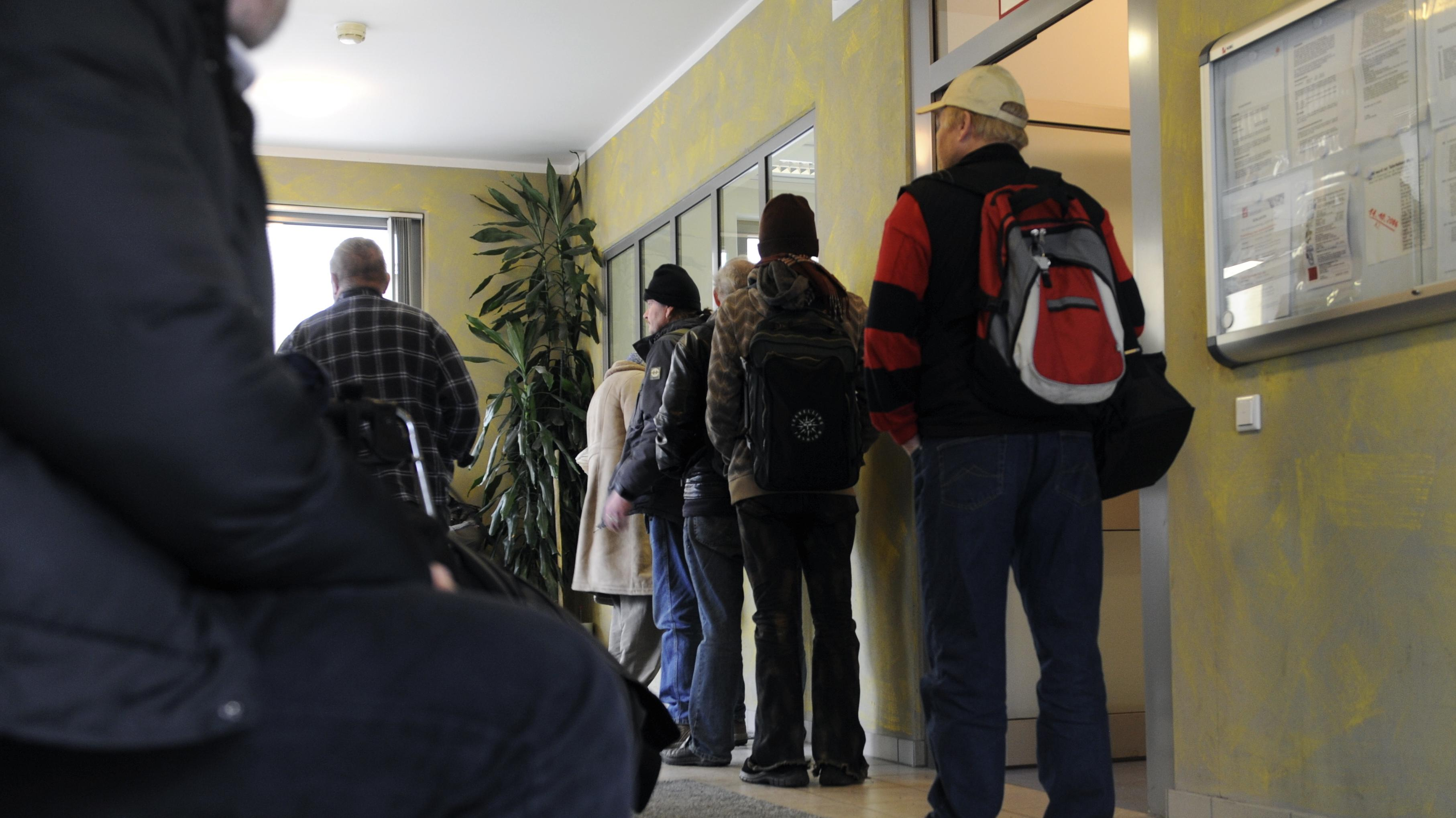 Männer warten in München an einem Schalter für die Zimmervergabe im Städtischen Unterkunftsheim für obdachlose Männer.