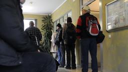 Männer warten in München an einem Schalter für die Zimmervergabe im Städtischen Unterkunftsheim für obdachlose Männer.  | Bild:dpa/Tobias Hase