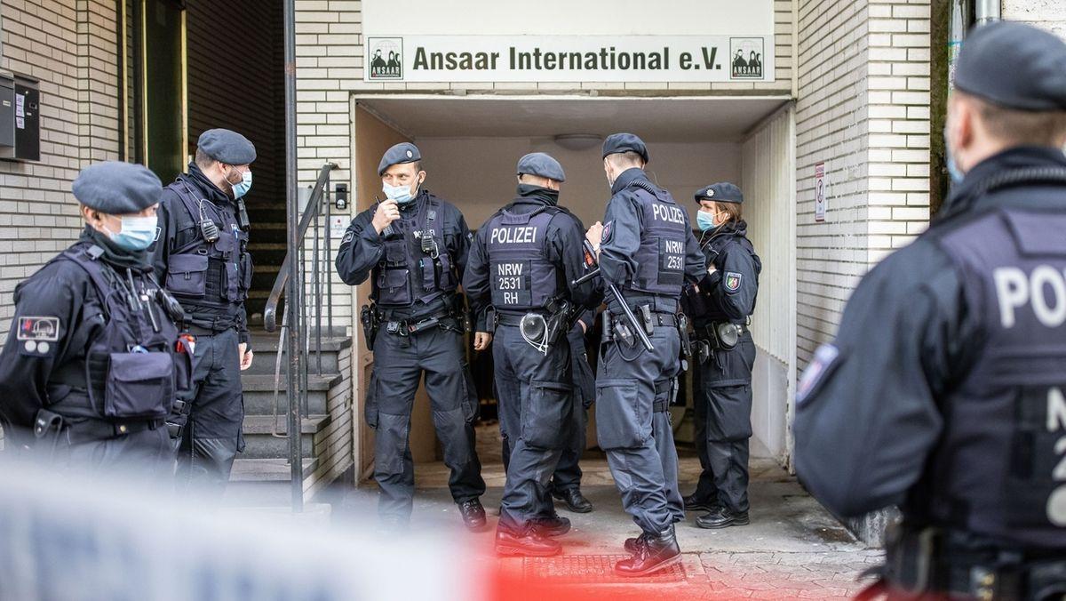 Polizeibeamte stehen vor dem Gebäude des Vereins Ansaar International.