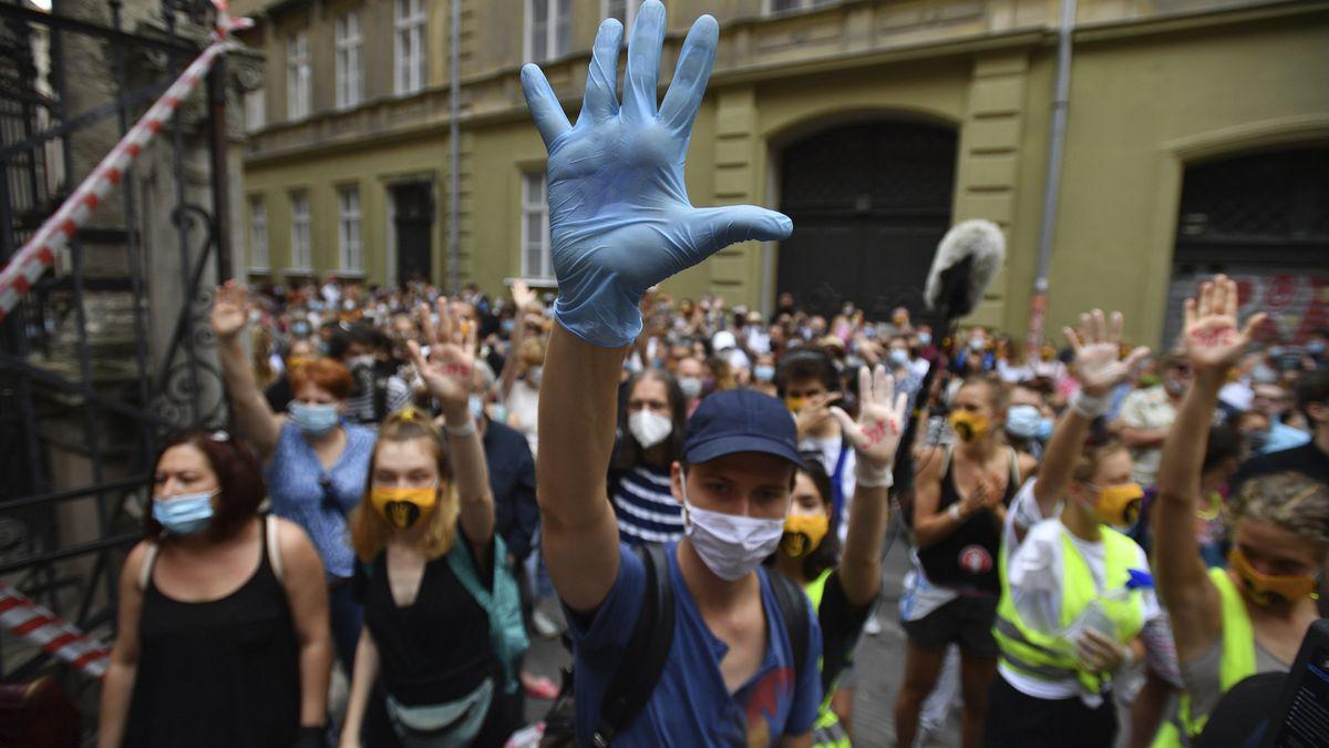 Ein junger Mann hält seine Hand wie ein Stoppschild in die Höhe, hinter ihm tun es ihm viele Demonstranten gleich.